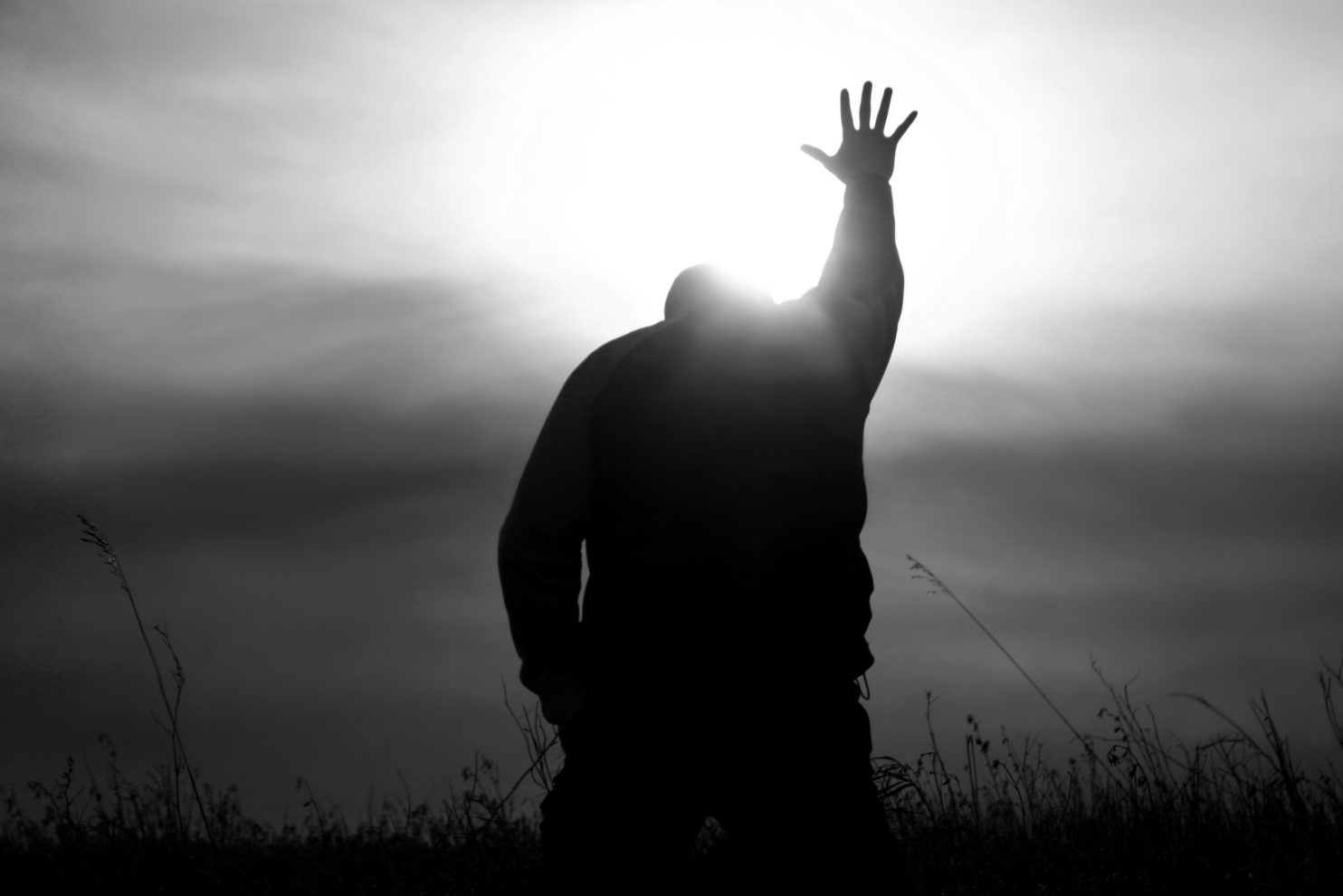 A man lifts his hand to heaven in worship. Black and white image depicting a Christian theme with man lifting his hand to heaven in praise. Powerful monochrome image. Additional themes include praise and worship, Christianity, hope, heaven, healing, miracles, salvation, faith, god, prayer, meditation, spirituality, afterlife, and forgiveness.
